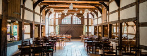 Innenansicht der Ramselhof-Tenne mit Tischen und Stühlen